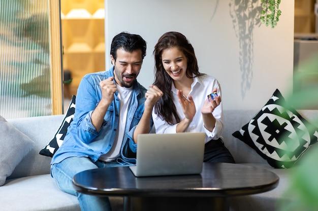 Heureux jeune couple familial faisant du shopping en ligne avec un ordinateur portable. faire des achats en ligne concept.
