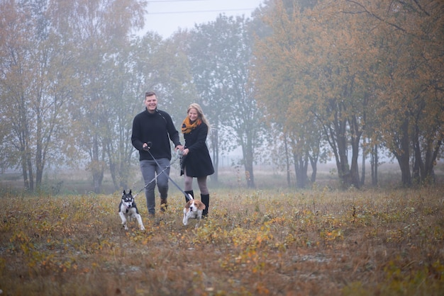 Heureux jeune couple de famille avec deux chiens courant dans le parc d'automne