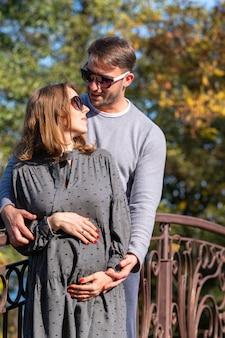 Heureux jeune couple avec une femme enceinte debout ensemble dans une étreinte étroite alors qu'elle berce son bébé bosse dans ses mains