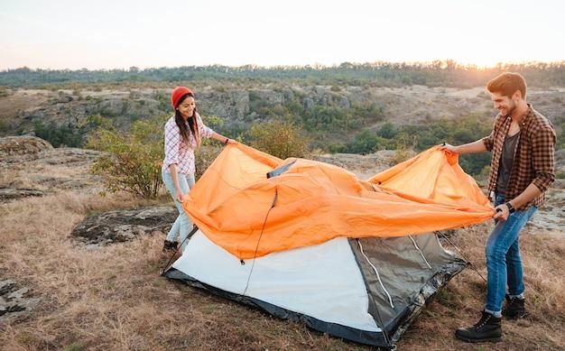 Heureux jeune couple fixant une tente à l'extérieur
