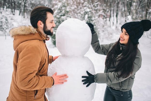 Heureux jeune couple en hiver. famille à l'extérieur. homme et femme regardant vers le haut et riant. amour, plaisir, saison et gens - marcher dans le parc d'hiver. faire un bonhomme de neige.