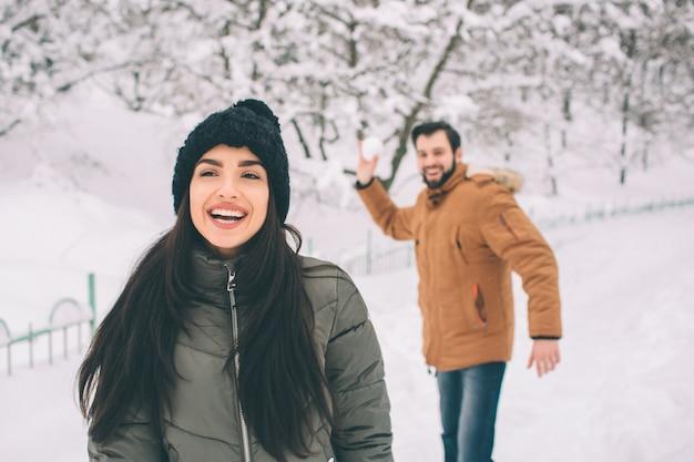 Heureux jeune couple en hiver. famille à l'extérieur. homme et femme regardant vers le haut et riant. amour, plaisir, saison et gens - marcher dans le parc d'hiver. il fait boule de neige