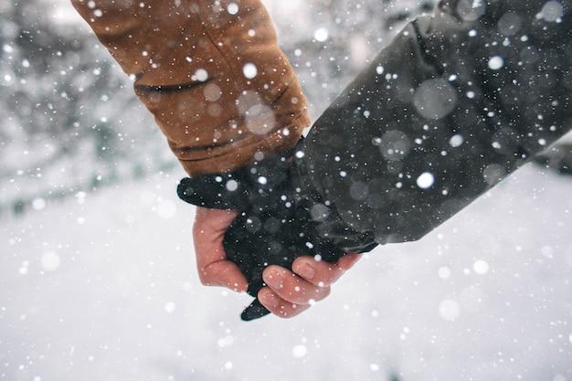 Heureux jeune couple en hiver. famille à l'extérieur. homme et femme regardant vers le haut et riant. amour, plaisir, saison et gens - marcher dans le parc d'hiver. tenant la main, gros plan.