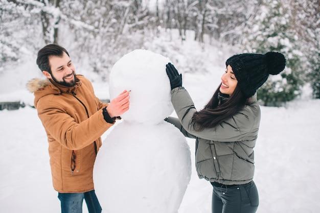 Heureux jeune couple en hiver. famille en plein air. homme et femme regardant vers le haut et en riant. amour, amusement, saisons et gens - promenade dans le parc d'hiver. faire un bonhomme de neige.