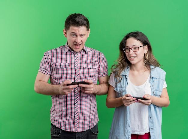 Heureux jeune couple homme et femme à l'aide de gadgets souriant debout sur le mur vert