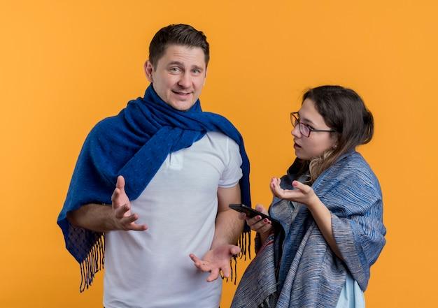 Heureux jeune couple homme et femme avec des couvertures faisant valoir debout sur un mur orange