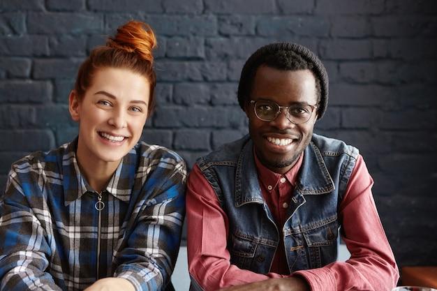 Heureux jeune couple interracial se détendre à l'intérieur