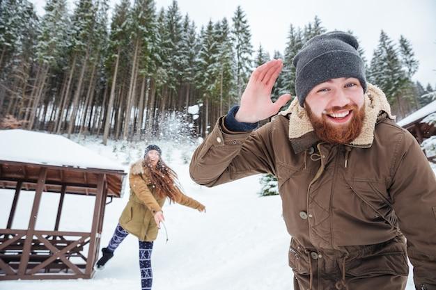 Heureux jeune couple jouant des boules de neige dans la forêt d'hiver