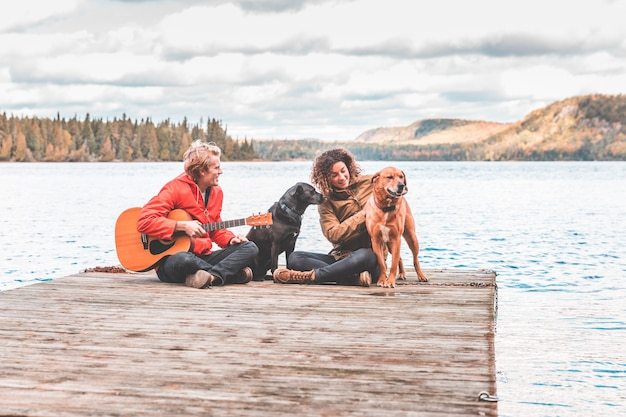 Heureux jeune couple jouant avec un chien sur un quai
