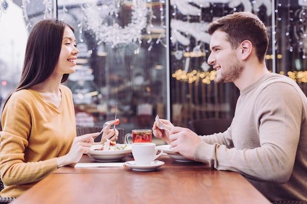 Heureux jeune couple joyeux manger des salades en riant et assis l'un en face de l'autre