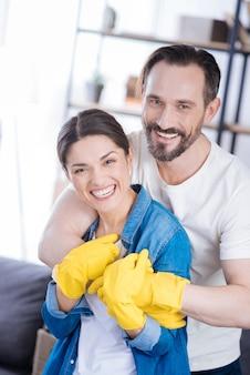 Heureux jeune couple joyeux portant des gants et posant sur l'arrière-plan flou en riant