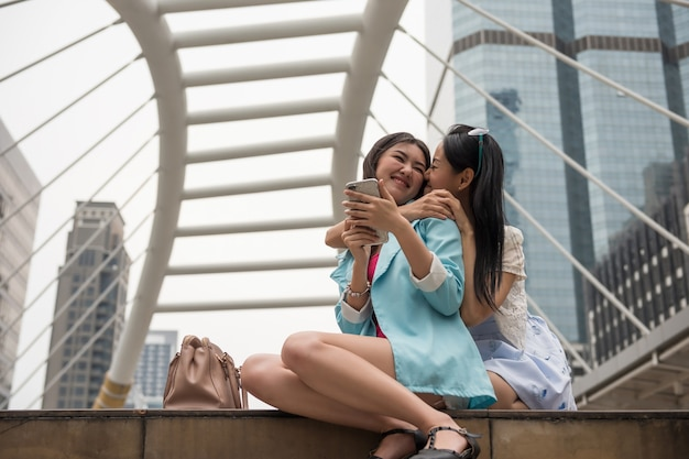 Heureux jeune couple de lesbiennes asiatiques s'embrassent et s'embrassent pendant la pause du shopping dans la ville urbaine. moment doux lgbt homosexuel en ville.