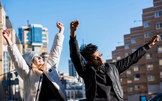 Heureux jeune couple levant leurs mains danser contre des bâtiments