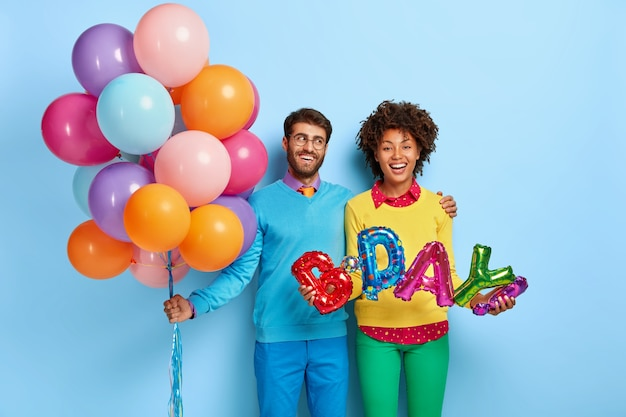 Heureux jeune couple lors d'une fête posant avec des ballons