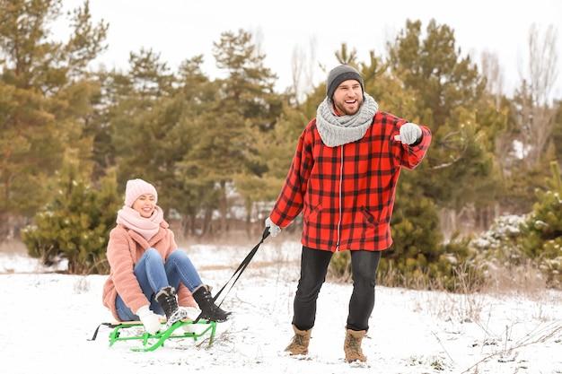 Heureux jeune couple de la luge dans le parc le jour de l'hiver