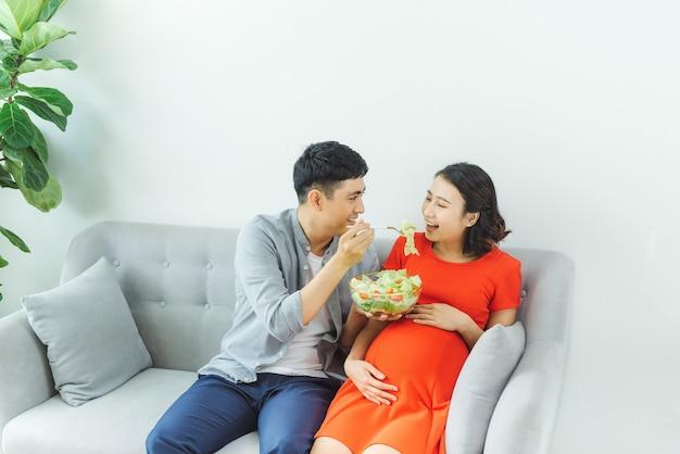 Heureux jeune couple mangeant de la salade ensemble au canapé dans le salon