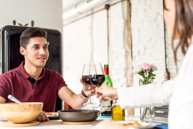 Heureux jeune couple manger et boire du vin à la maison