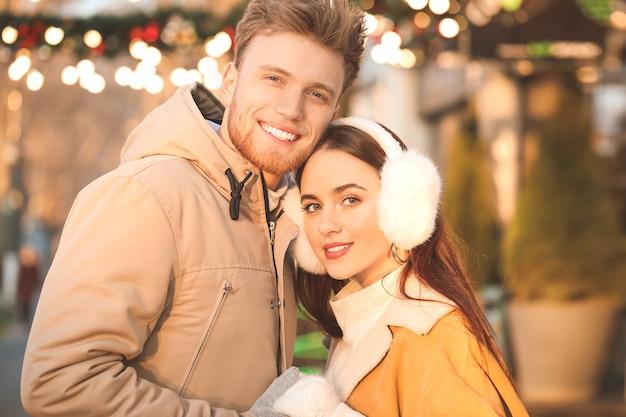 Heureux jeune couple marchant à l'extérieur le jour de l'hiver