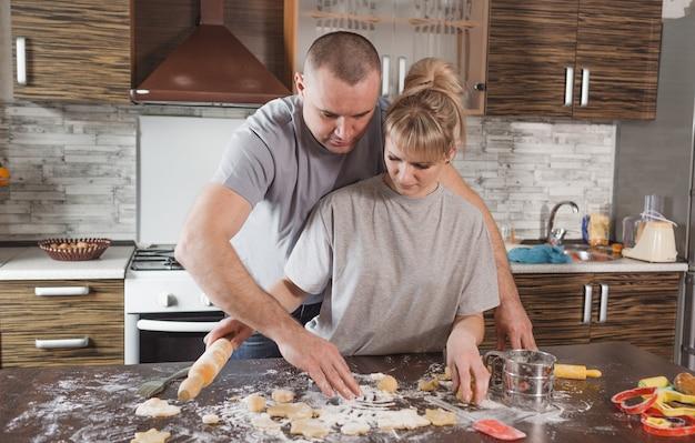 Heureux jeune couple mari et femme ensemble, s'amusant à faire des biscuits à la maison dans la cuisine. joie et compréhension mutuelle dans la famille.