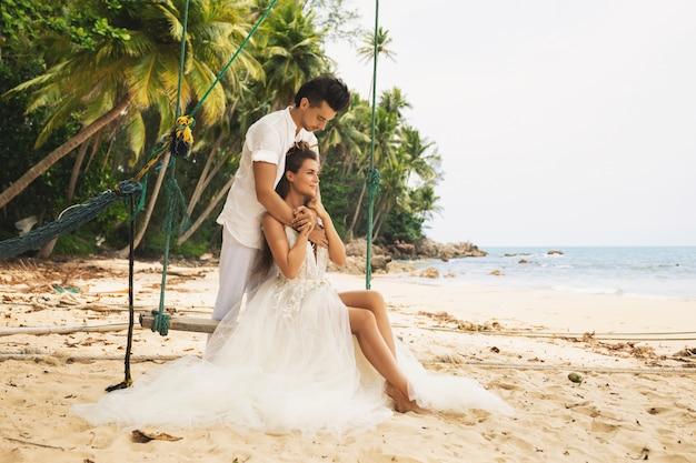 Heureux jeune couple marié célébrant leur mariage sur la plage