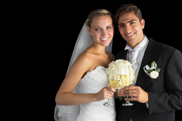 Heureux jeune couple marié posant tenant des verres de champagne