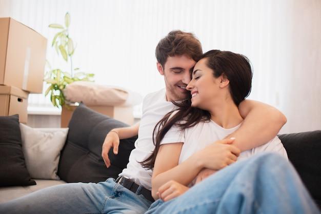 Heureux jeune couple marié s'installe dans un nouvel appartement. ils sont assis sur le canapé et regardent leur nouvelle maison.