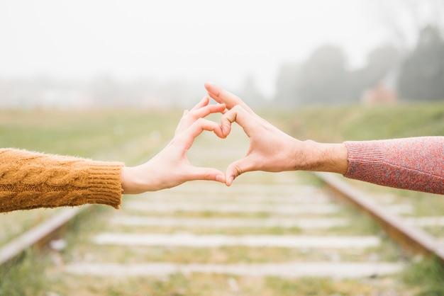 Heureux jeune couple montrant le geste du coeur