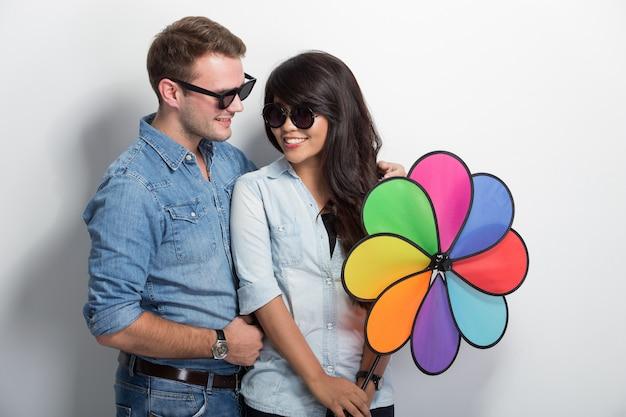 Heureux jeune couple de multiculture posant avec moulin à vent