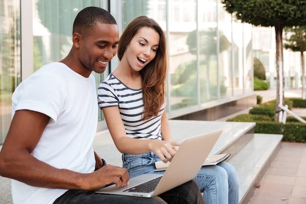Heureux jeune couple multiethnique parlant et utilisant un ordinateur portable à l'extérieur