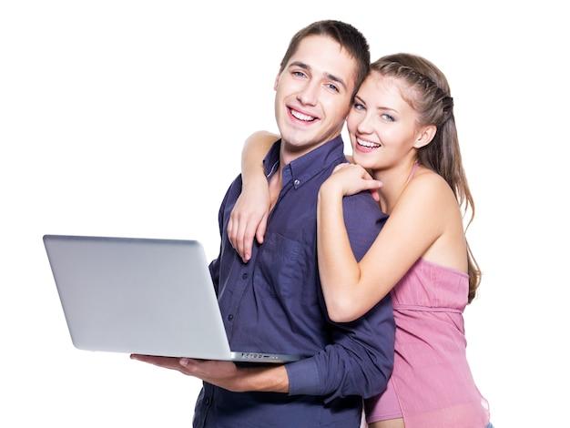 Heureux jeune couple avec ordinateur portable sur fond blanc