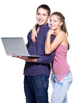 Heureux jeune couple avec ordinateur portable sur mur blanc