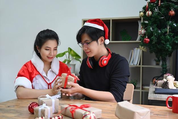 Heureux jeune couple ouvrant le cadeau de noël dans le salon au moment de noël.