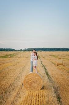 Heureux jeune couple sur la paille, concept de personnes romantiques, beau paysage, saison estivale.