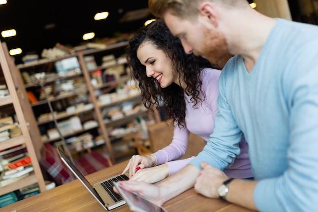 Heureux jeune couple passant du temps au café travaillant sur ordinateur portable