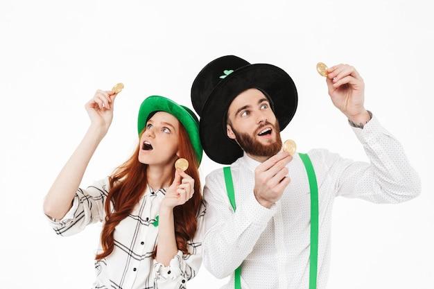 Heureux jeune couple portant des costumes, célébrant la saint-patrick isolé sur mur blanc, tenant des bitcoins dorés