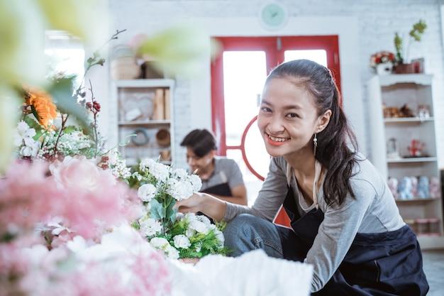Heureux jeune couple portant un tablier souriant en regardant la caméra. travaillant dans un magasin de fleurs avec un ami derrière