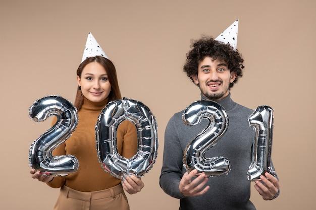 Heureux jeune couple porter chapeau de nouvel an posant avec dans leurs mains sur gris