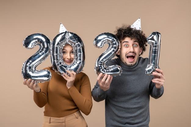Heureux, jeune couple, porter, chapeau nouvel an, poses, pour, appareil photo, girl, projection, et, gars, à, et, sur, gris banque de photo