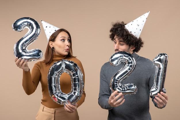 Heureux jeune couple porter des poses de chapeau de nouvel an pour caméra fille