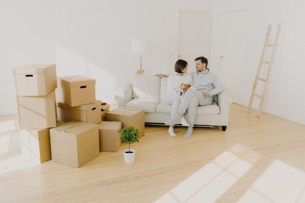 Heureux jeune couple pose ensemble sur un canapé confortable, avoir une conversation agréable, taquiner le chien