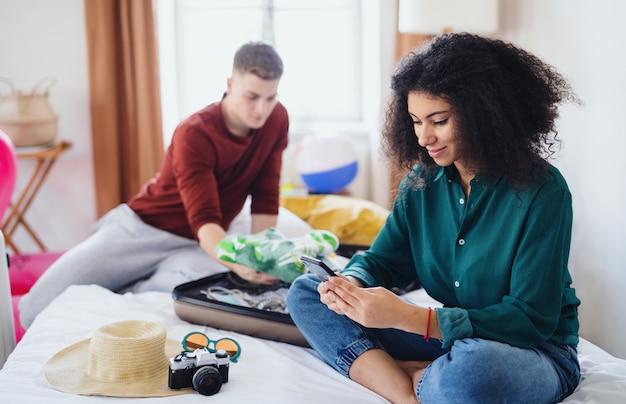 Heureux jeune couple préparant et emballant pour les vacances d'été à la maison.