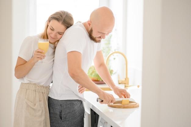 Heureux jeune couple prépare le petit déjeuner et s'amuse.