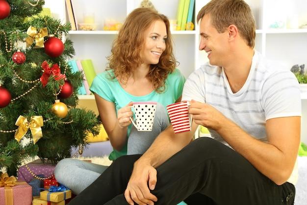 Heureux jeune couple près de l'arbre de noël à la maison