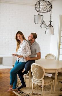 Heureux, jeune couple, regarder, tablette numérique, dans, salle de séjour