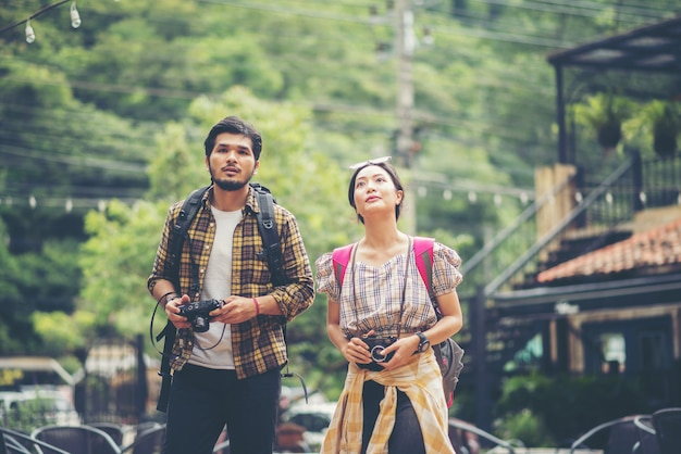 Heureux jeune couple de routards se promener ensemble dans la rue