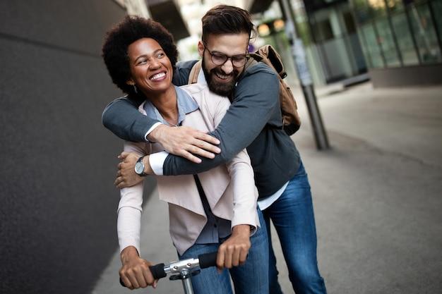 Heureux jeune couple s'amusant ensemble tout en conduisant des scooters électriques dans la rue de la ville