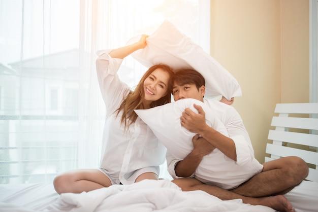 Heureux jeune couple s'amuse au lit