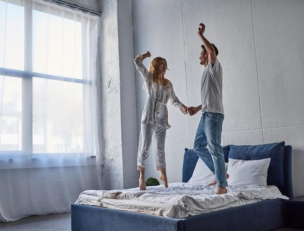 Heureux jeune couple s'amuse dans la chambre. profiter de la compagnie les uns des autres en sautant sur le lit