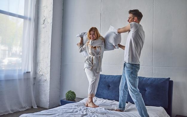 Heureux jeune couple s'amuse dans la chambre. profiter de la compagnie les uns des autres. sauter sur le lit pendant une bataille d'oreillers