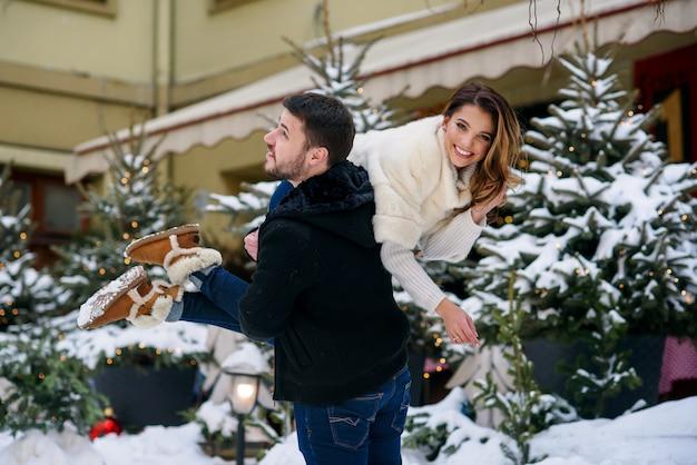 Heureux jeune couple s'amuser sur le paysage d'hiver de l'arbre de noël avec des lumières. vacances d'hiver, noël et nouvel an.